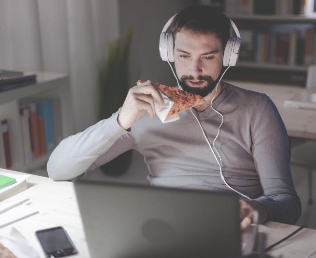man eating pizza at night