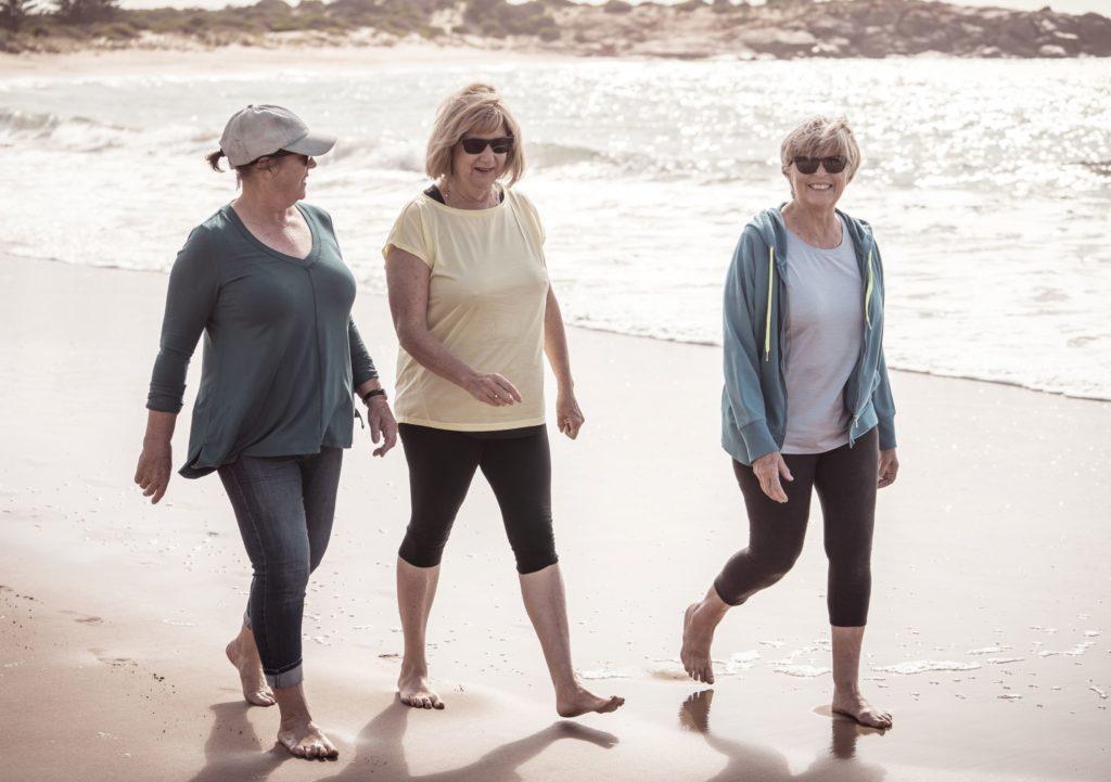older women walking on beach